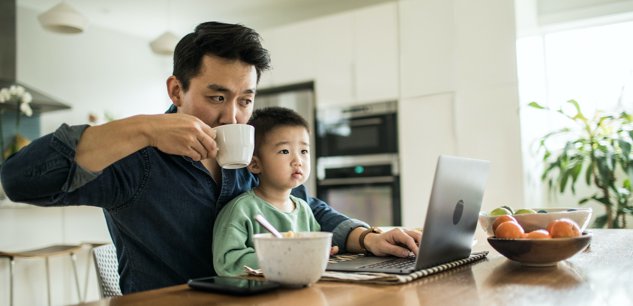 Father multitasking at computer with child in lap.