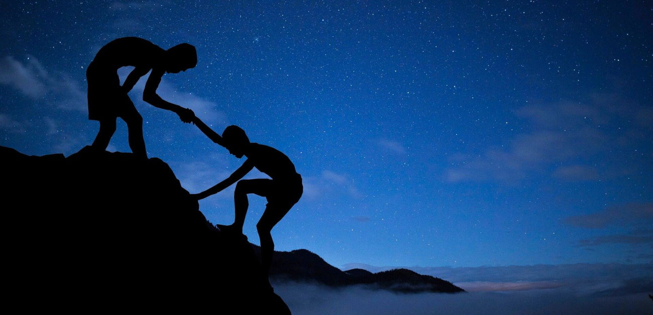 Photo illustration of a climber assisting another climber