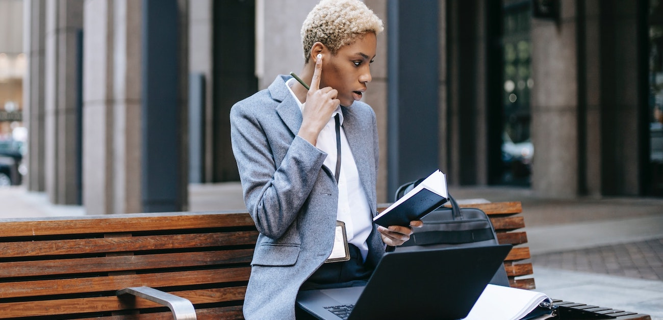 Woman sitting on bench talking on phone while on computer