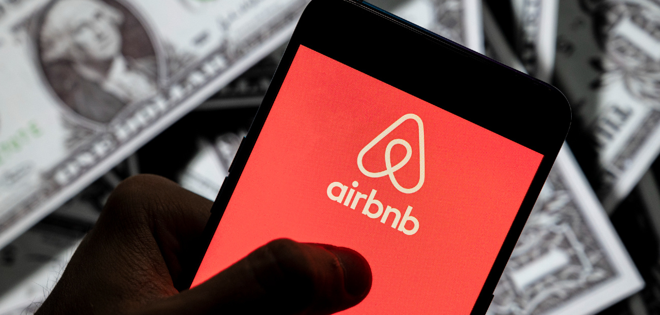 A picture of a hand holding a smartphone with the Airbnb logo over a background of dollar bills