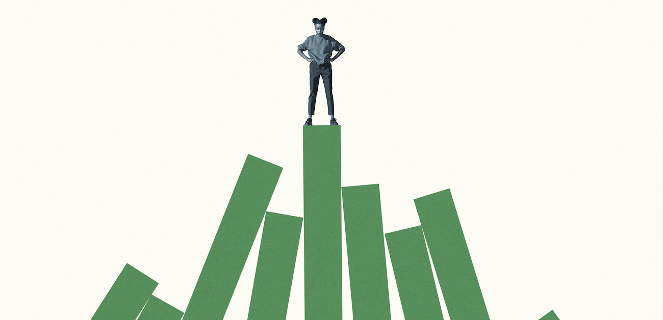 Woman standing on top of tall green bar graph.
