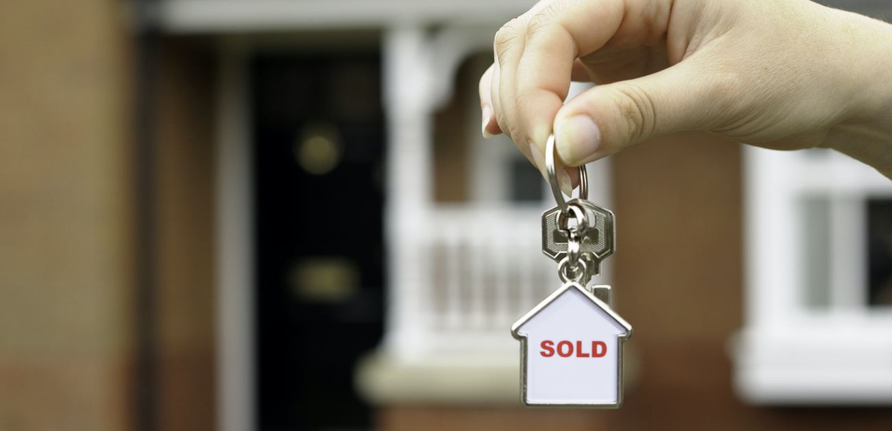 Woman holding keys with sold keyring in front of house.