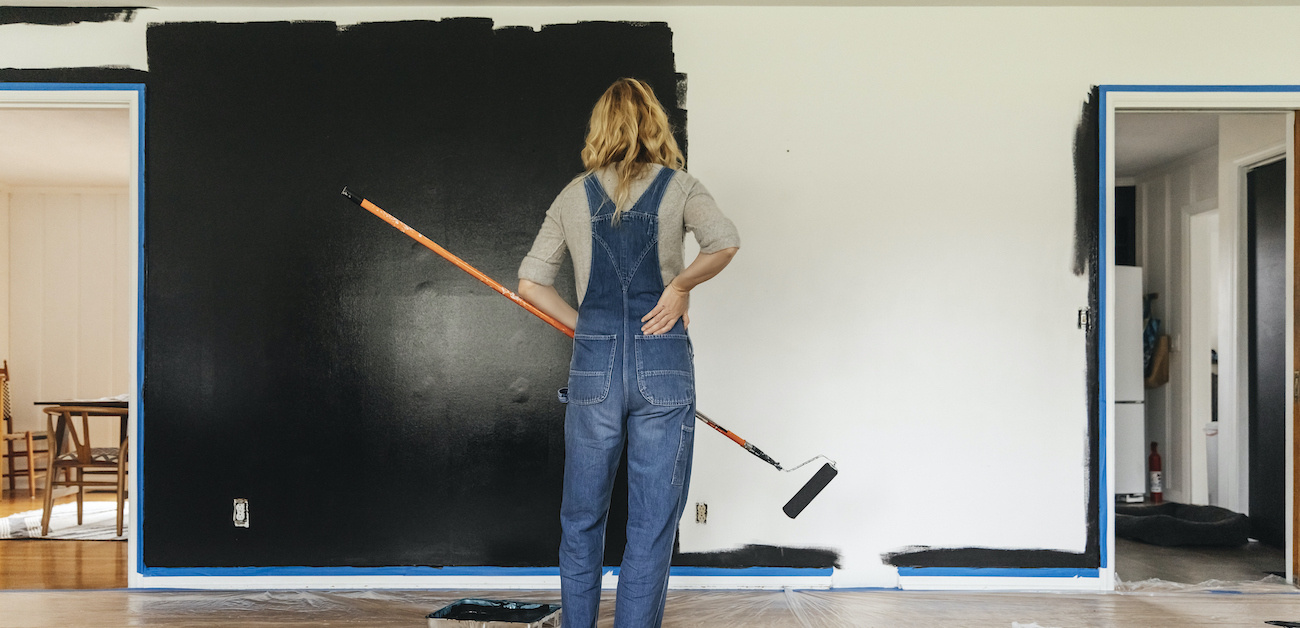 A woman standing in front of an interior house wall half painted black and half unfinished while holding a paint roller.