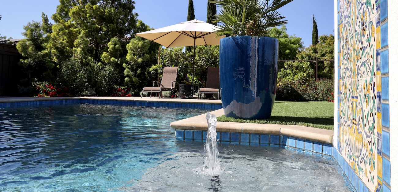Pool with fountain and tile embellishments.