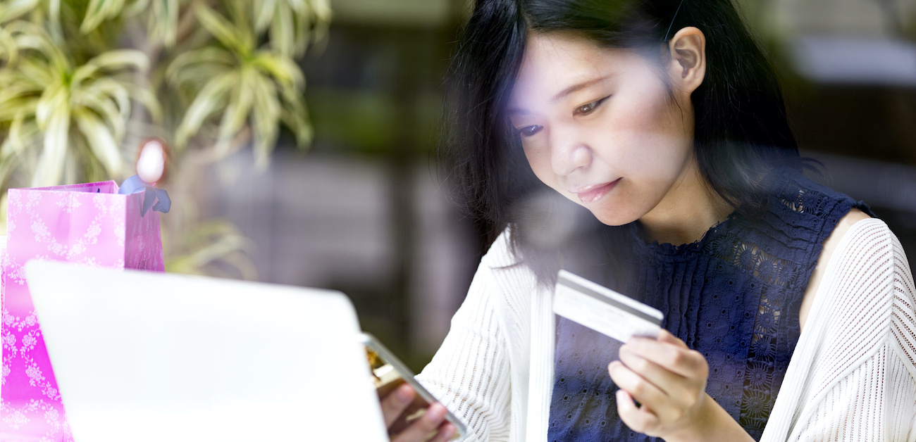 Woman holding credit card in front of computer