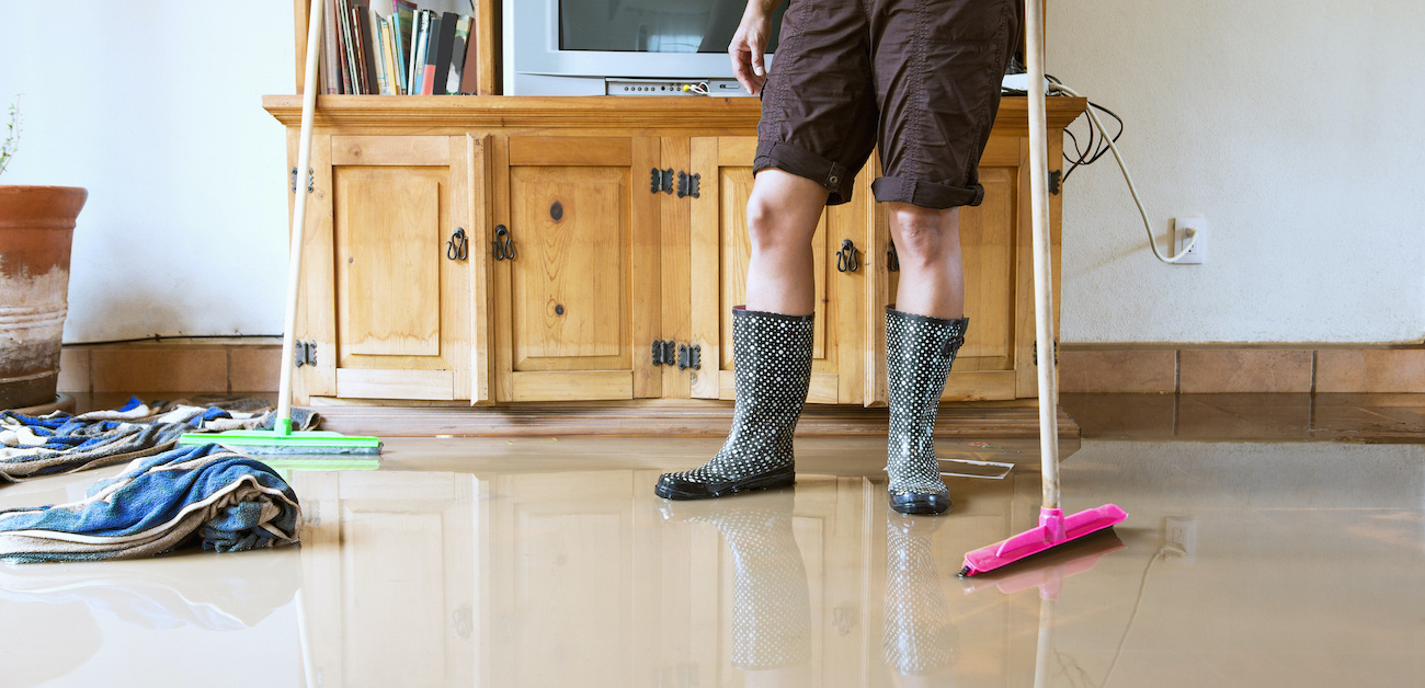 Woman wearing rainboots stands in flooding house