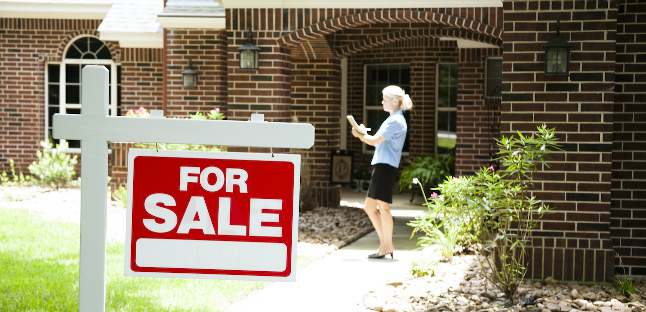 House with for sale sign in yard