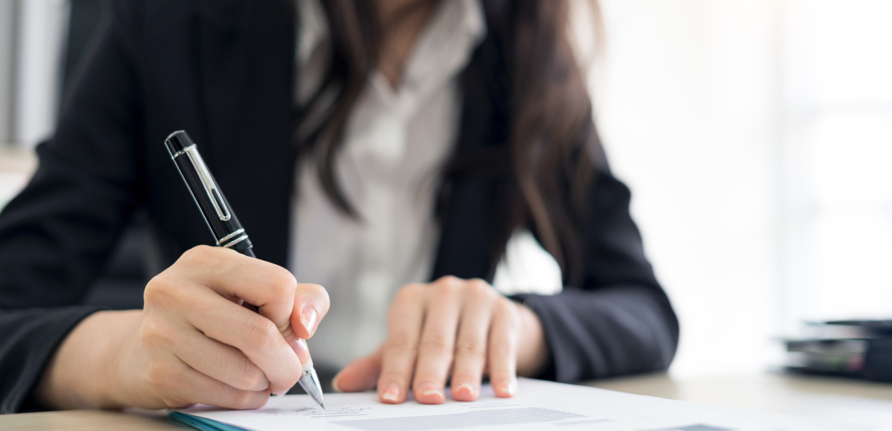 A woman signing documents