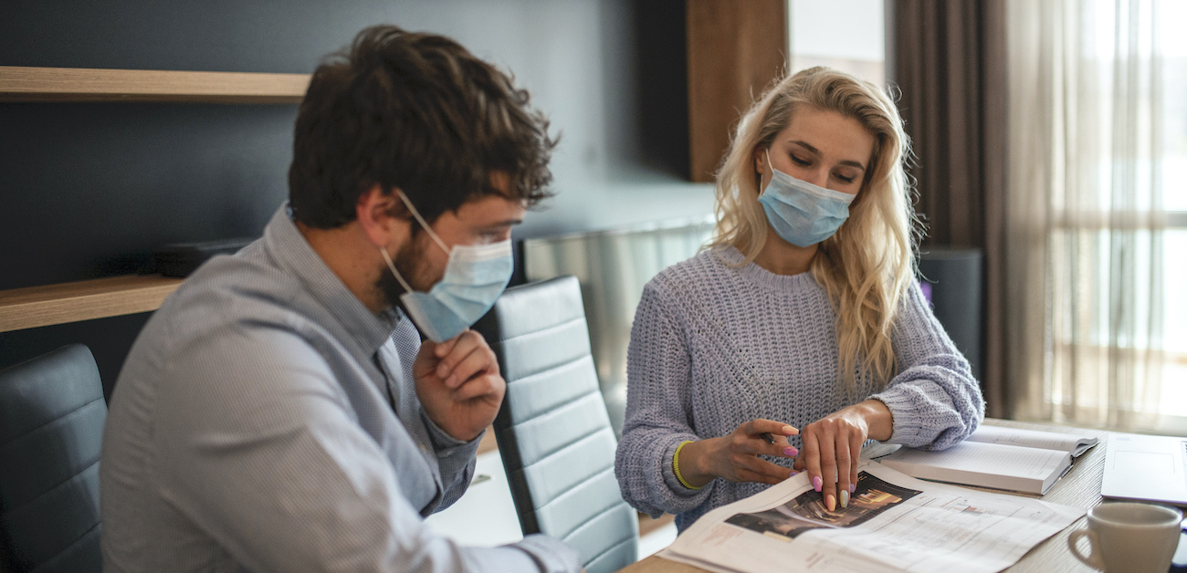 Real estate agents working with a client in an office wearing masks