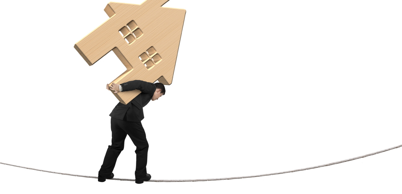 A man carrying a wooden model home on his back as he walks a tightrope