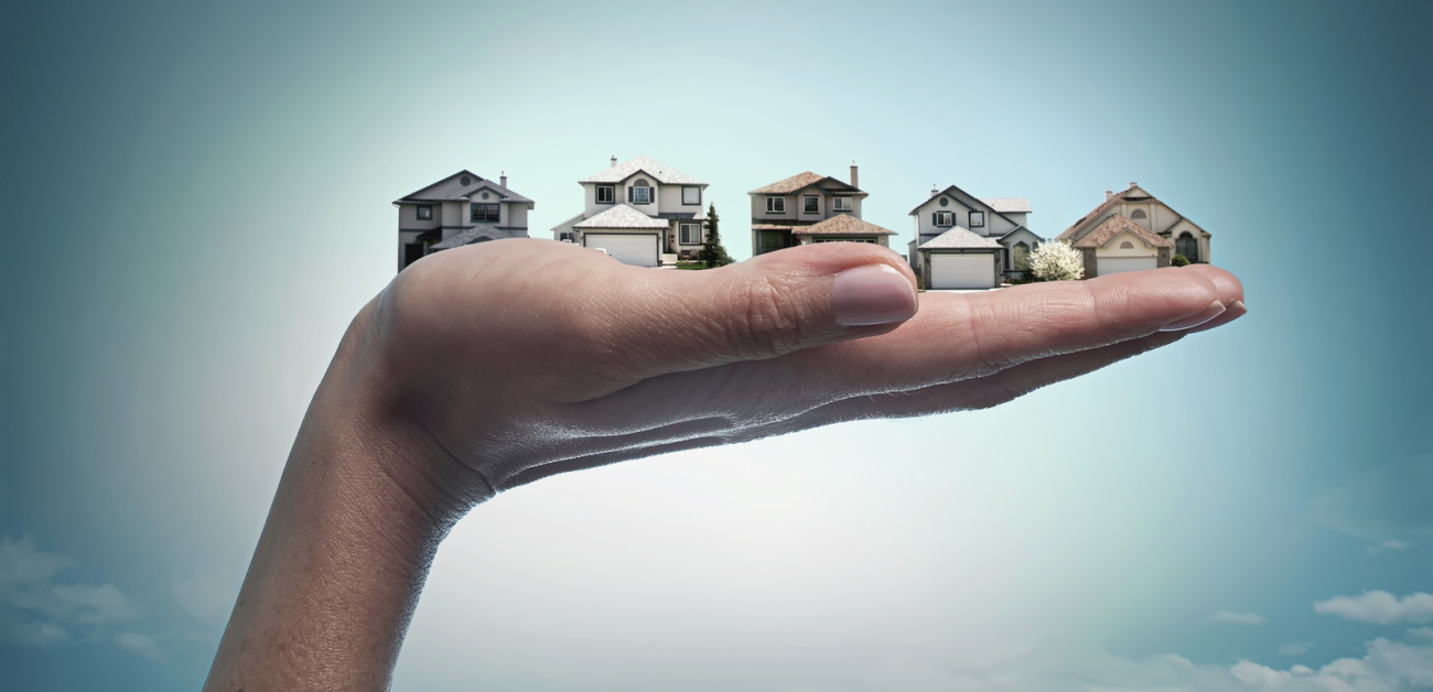 An image of a hand holding five different houses