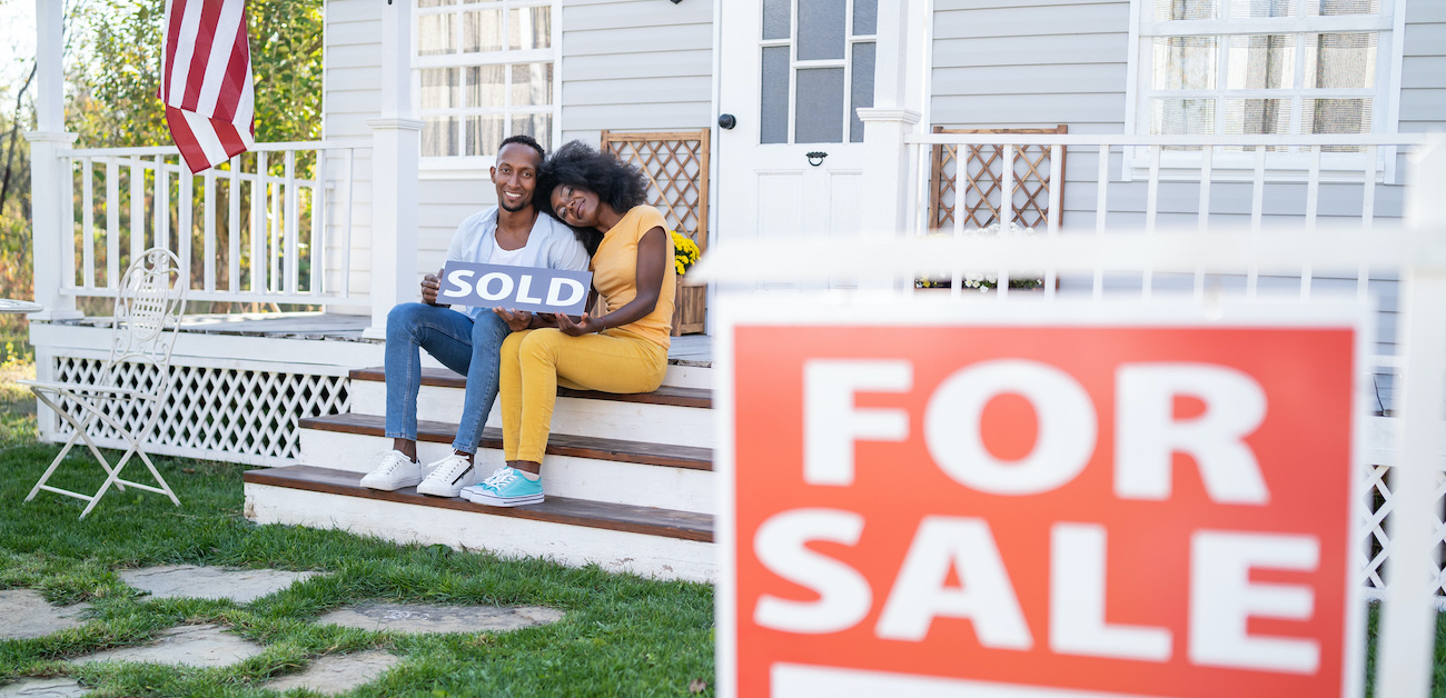 Couple sitting on steps with sold sign