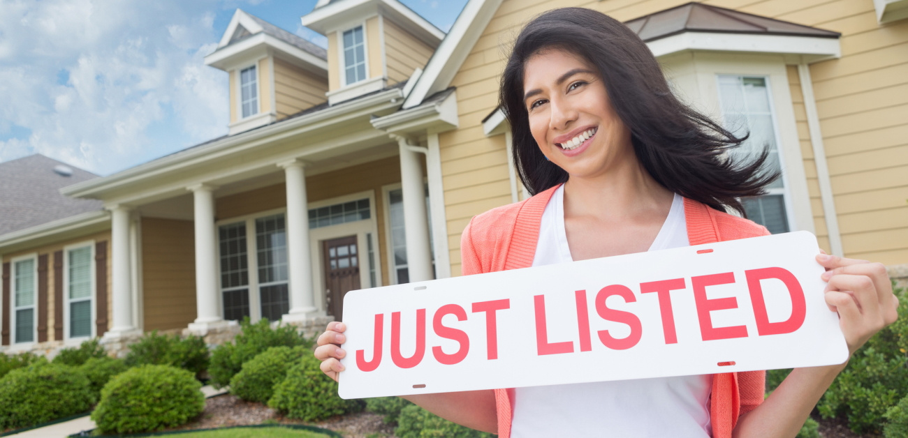 """Woman holding """"Just Listed"""" sign in front of single-family home"""