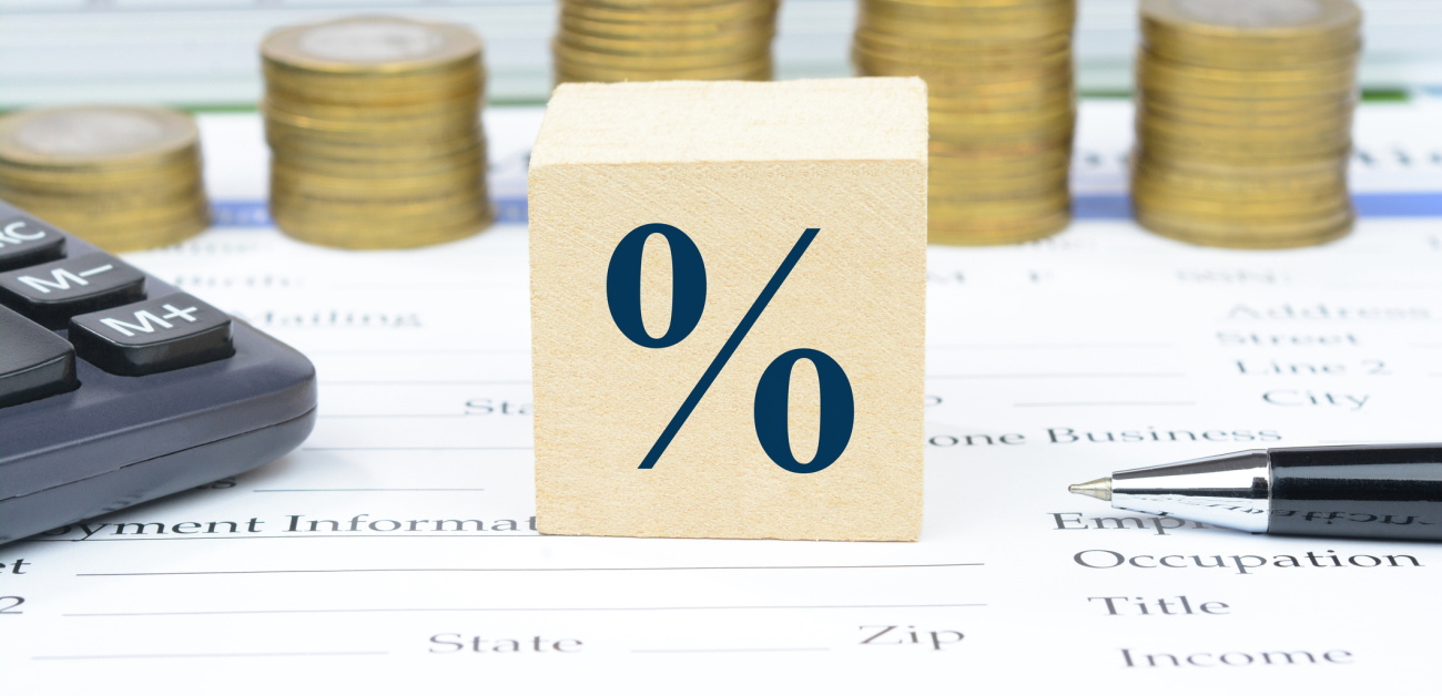 A percent sign on a block surrounded by stacks of coins, a calculator, and a pen