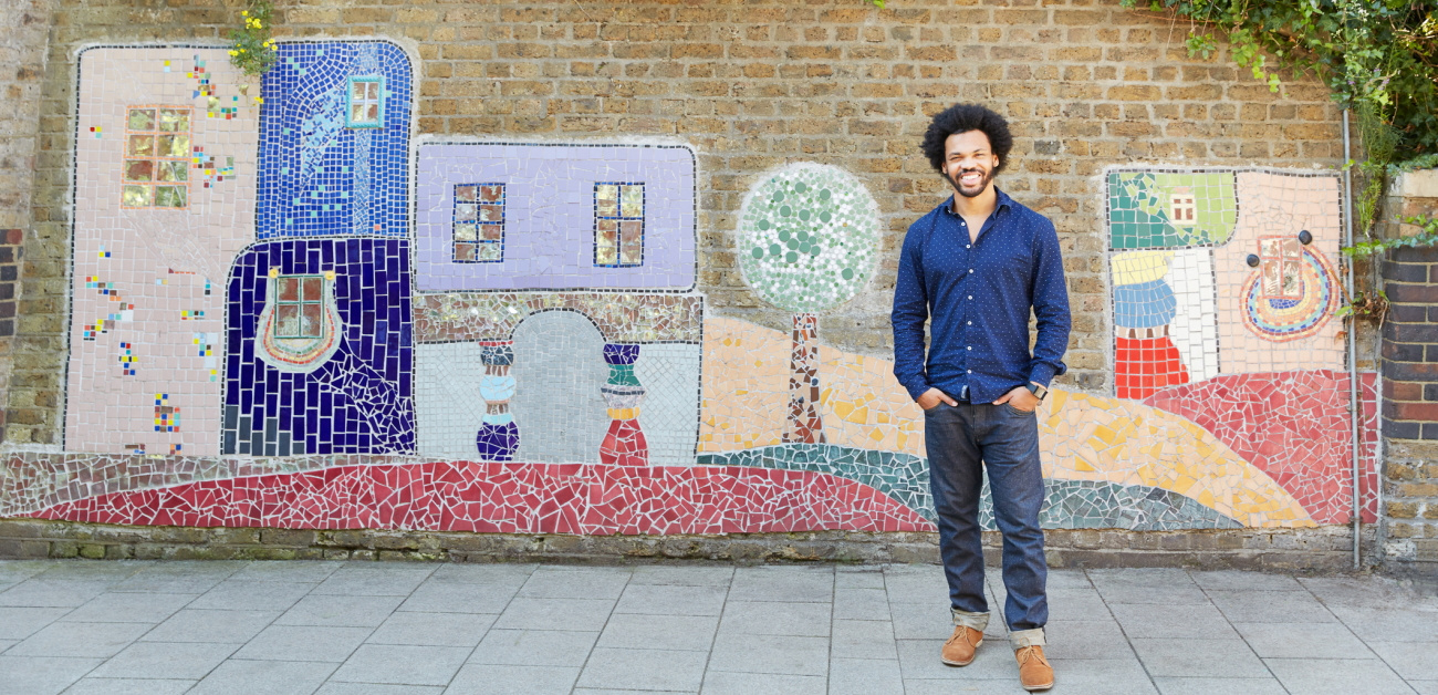 A man poses in front of an outdoor mural
