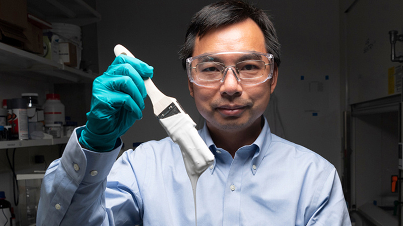 Xiulin Ruan, a Purdue University professor of mechanical engineering, holding a paint brush of the newly created white paint.