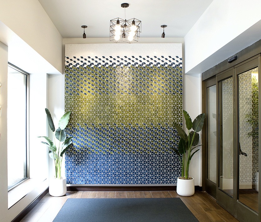A gradient tile art piece of geometric patterns composed of sage greens and blues adds texture to the space.
