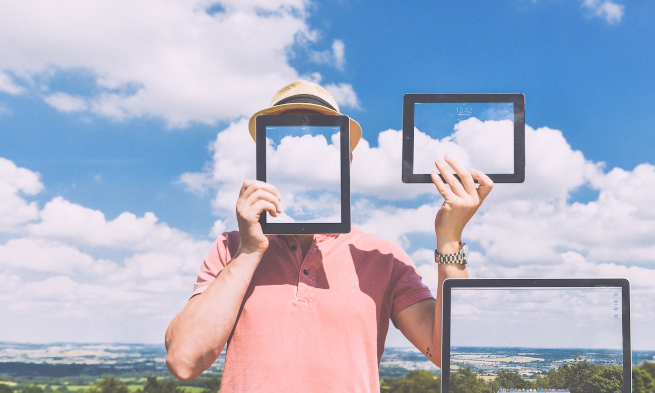 Man with blanked-out face holds empty screens