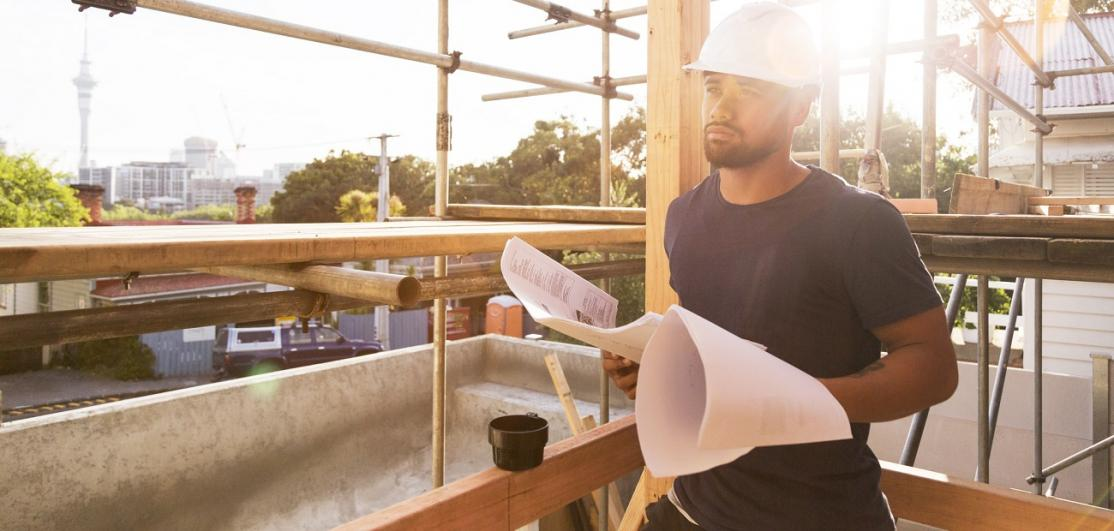 construction worker looks at building plans