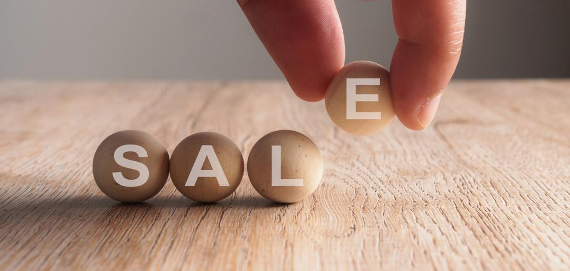 Hand Arranging Balls With Sale Text On Wooden Table