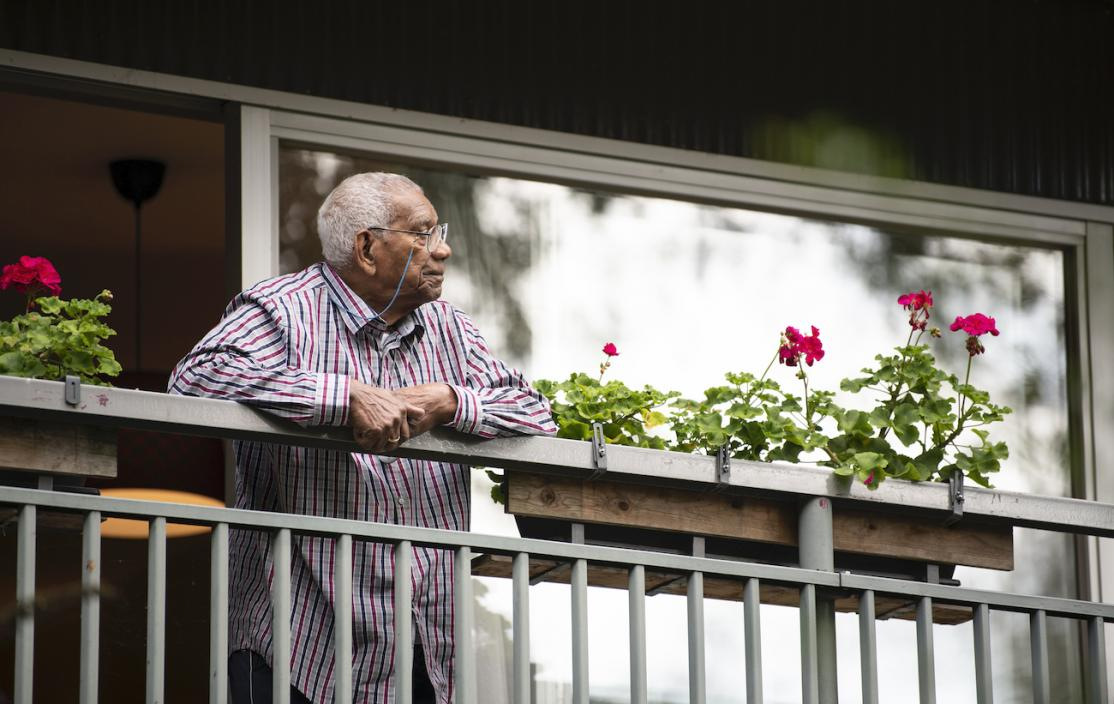 Old man leaning on balcony