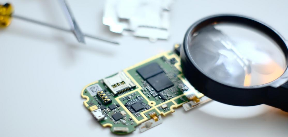 A magnifying glass over a computer circuit board