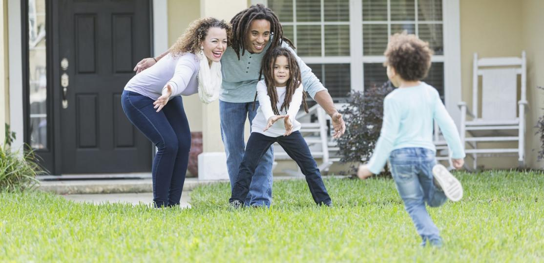 Mixed race family playing in front yard of home