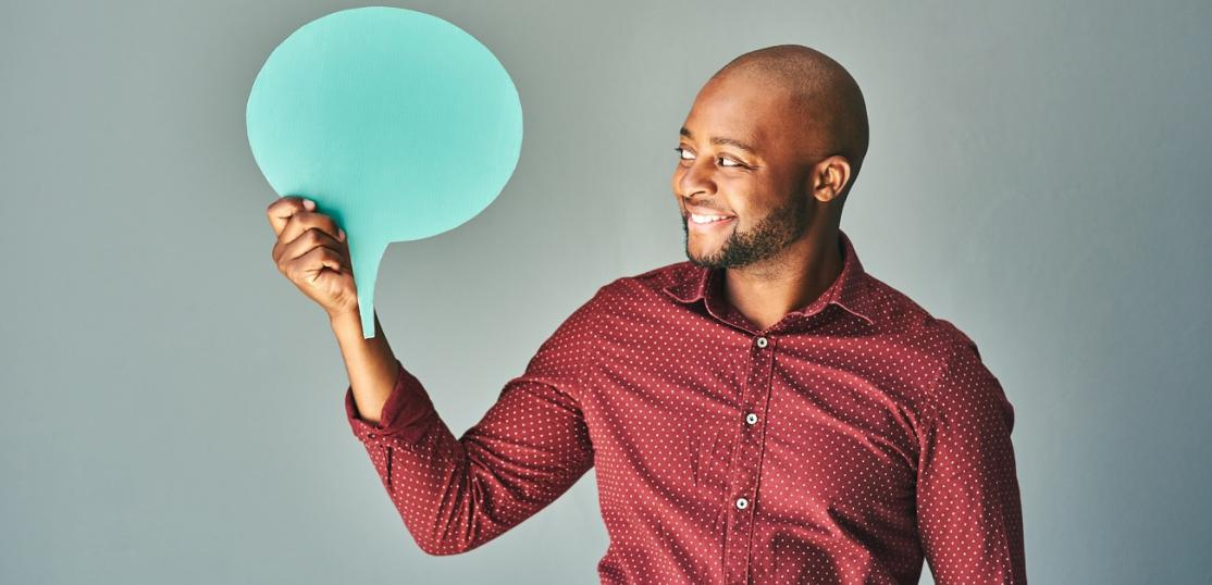 young man holding a speech bubble