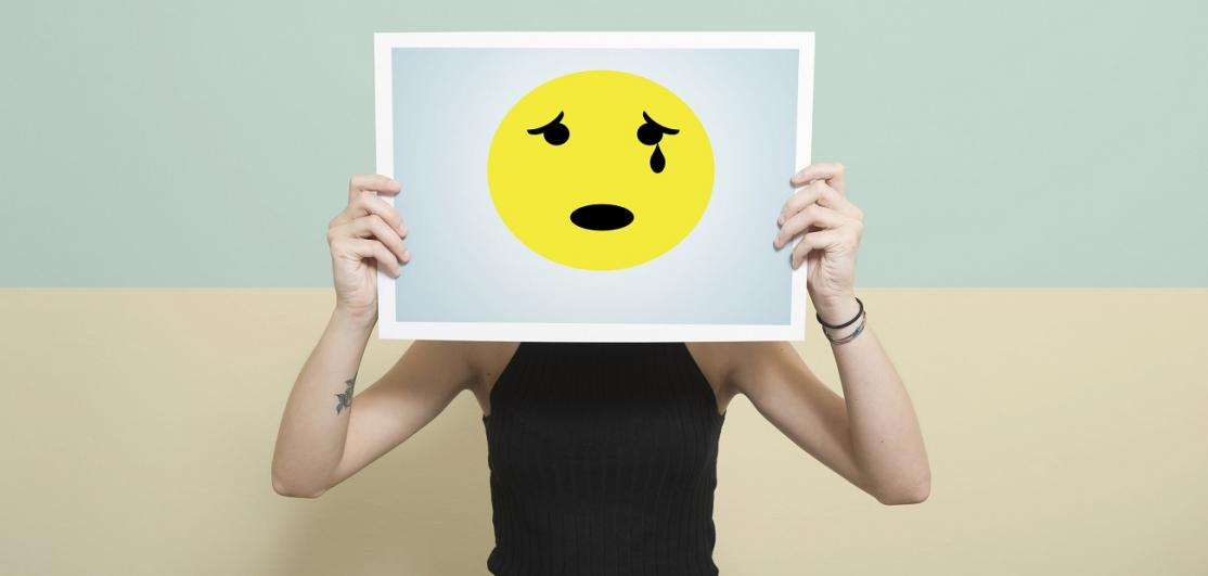 Woman stands behind a print of a crying anthropomorphic face