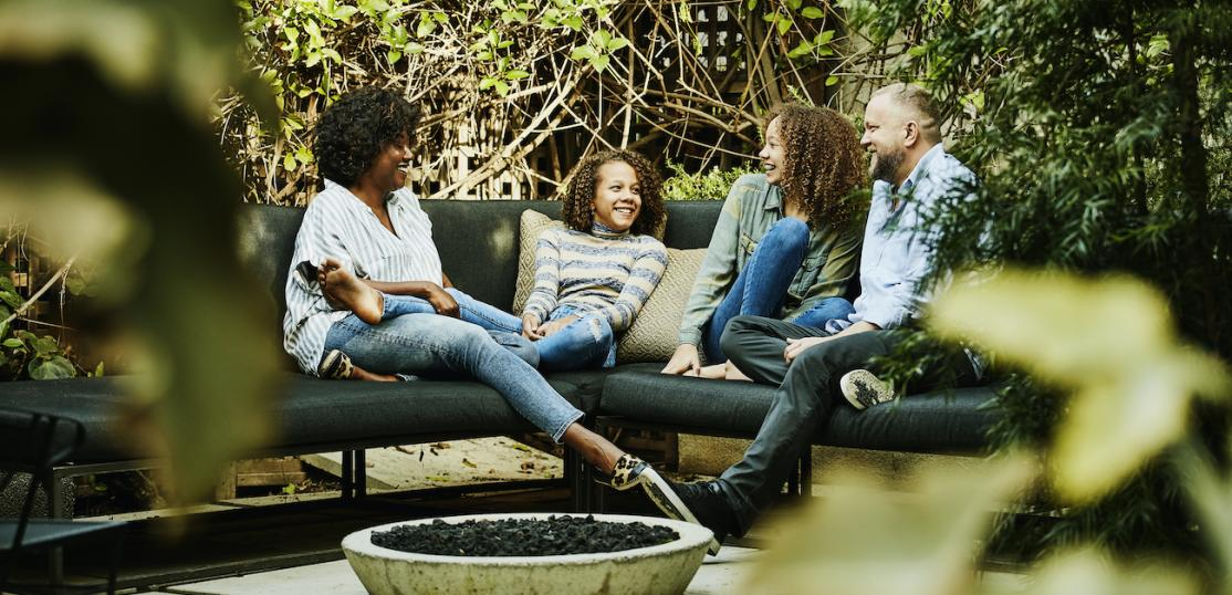 Family of four sitting on outdoor patio.