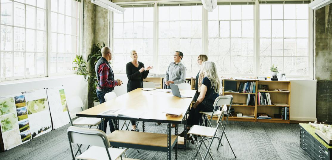 Broker talking to four agent around table