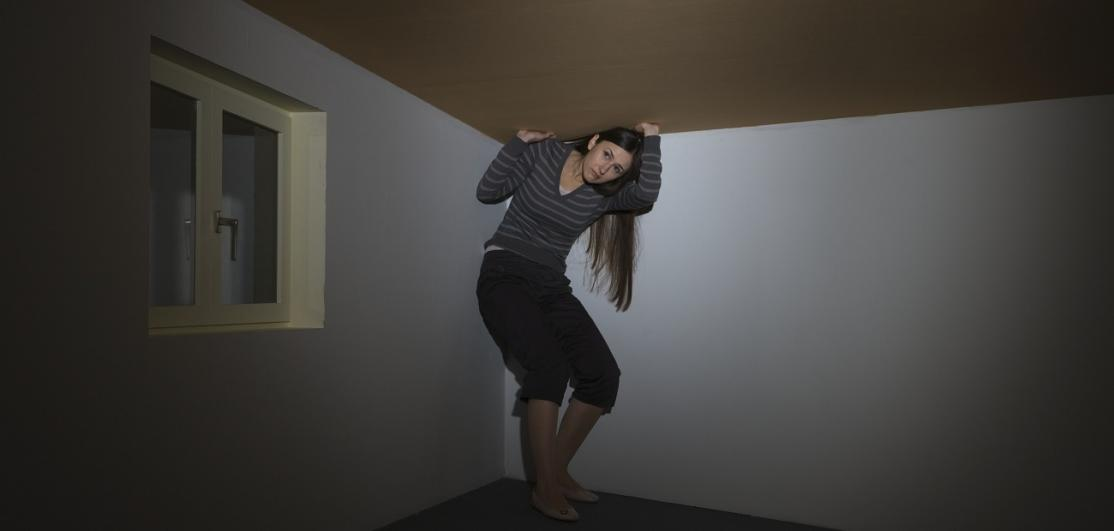 Woman trying to stand under low ceiling