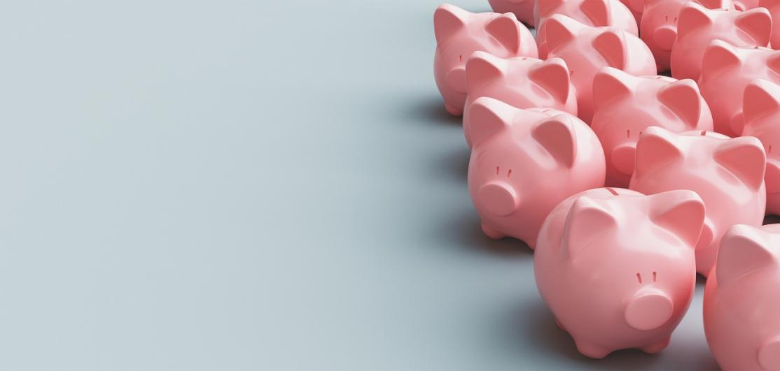 Close-Up Of Piggy Banks Over Gray Background
