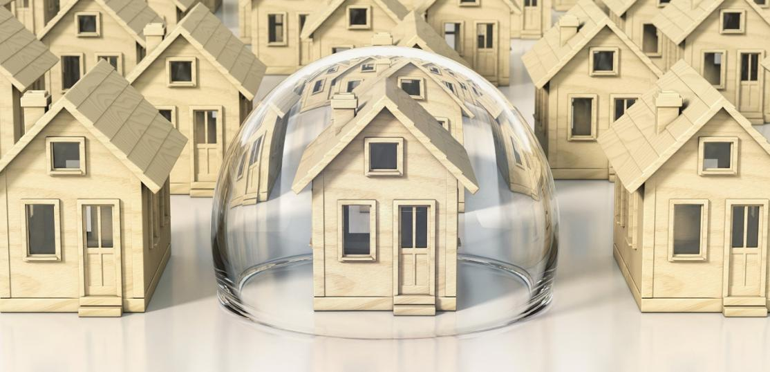 An illustrated graphic of a set of identical wooden houses with a bubble around the primary house in the center.