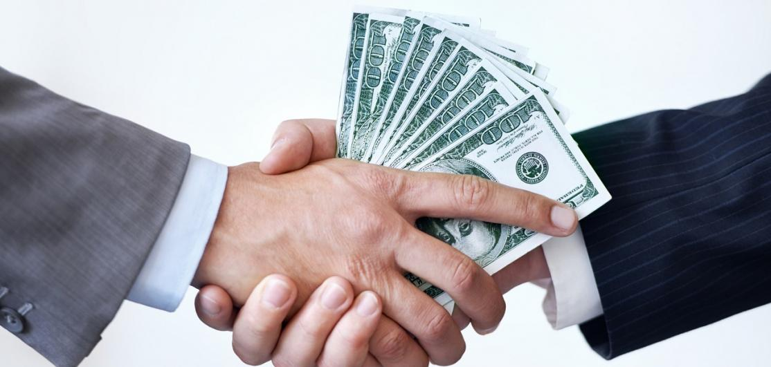 Two people shake with money in hand