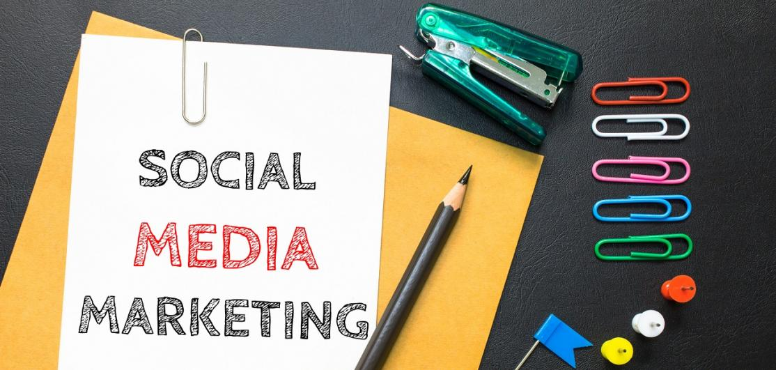 """Social Media Marketing"" on clipboard with office supplies"