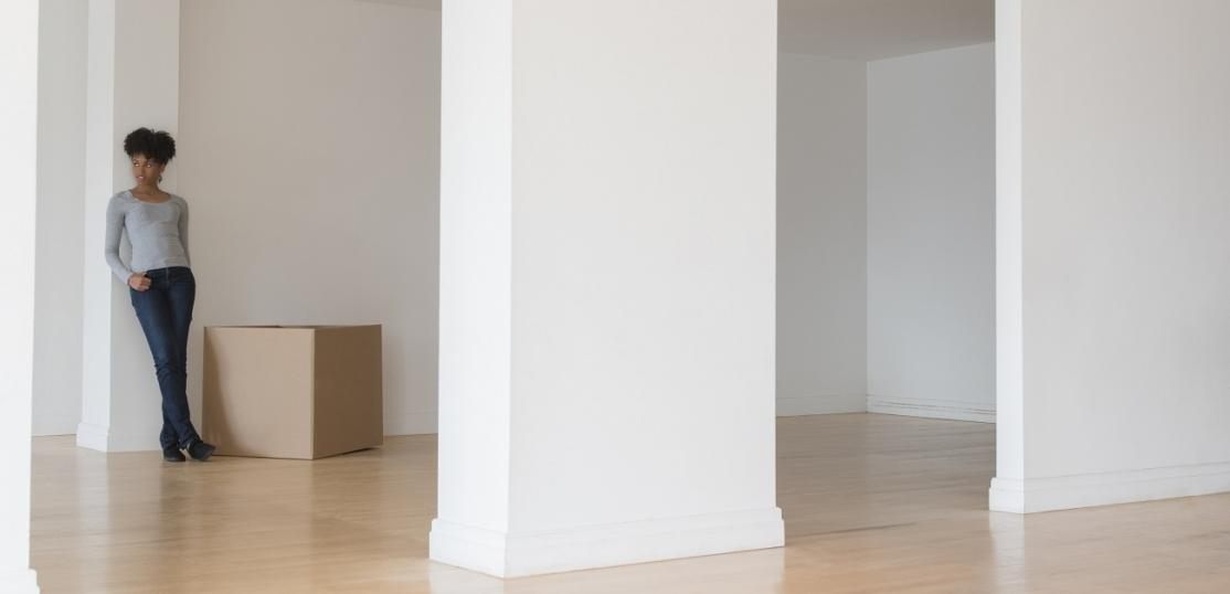 woman leaning on pillar in empty apartment