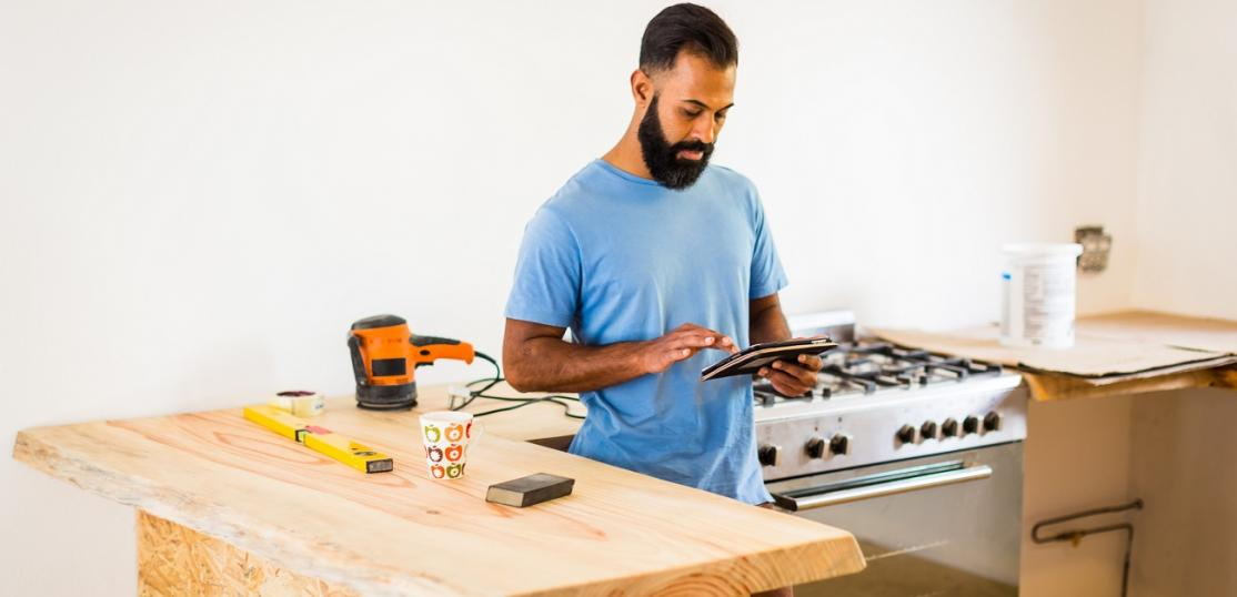 Man doing DIY in kitchen with tablet computer