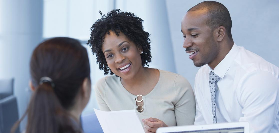 Couple smiling and talking with loan officer