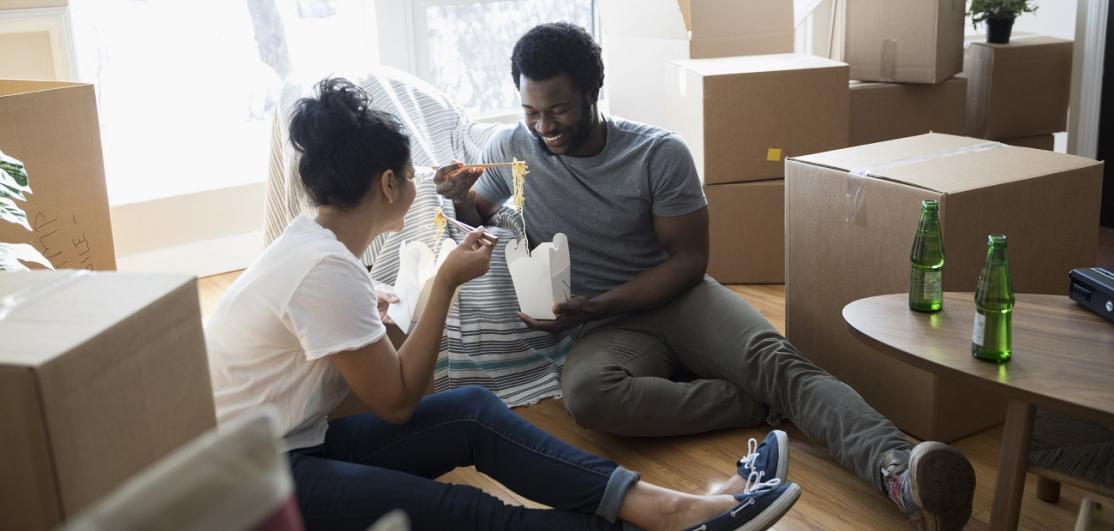 Couple eating with moving boxes at home