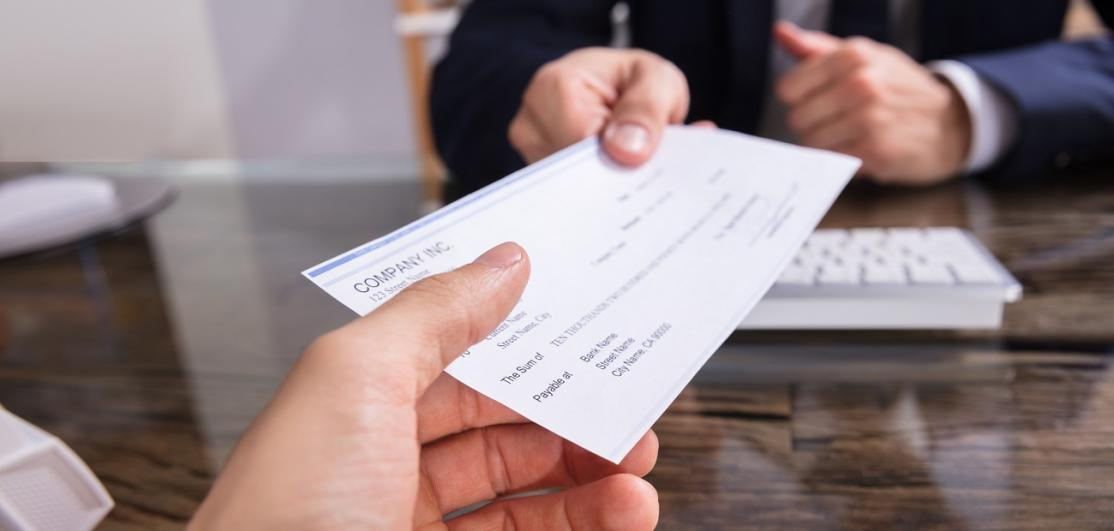 Businessperson Giving Check To Colleague