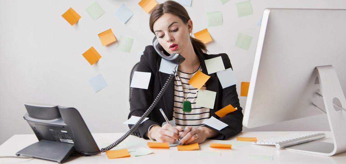 young woman working in office covered with adhesive notes