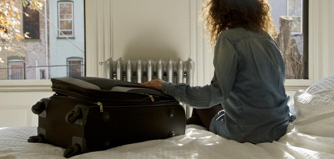 Woman with a suitcase sitting on bed