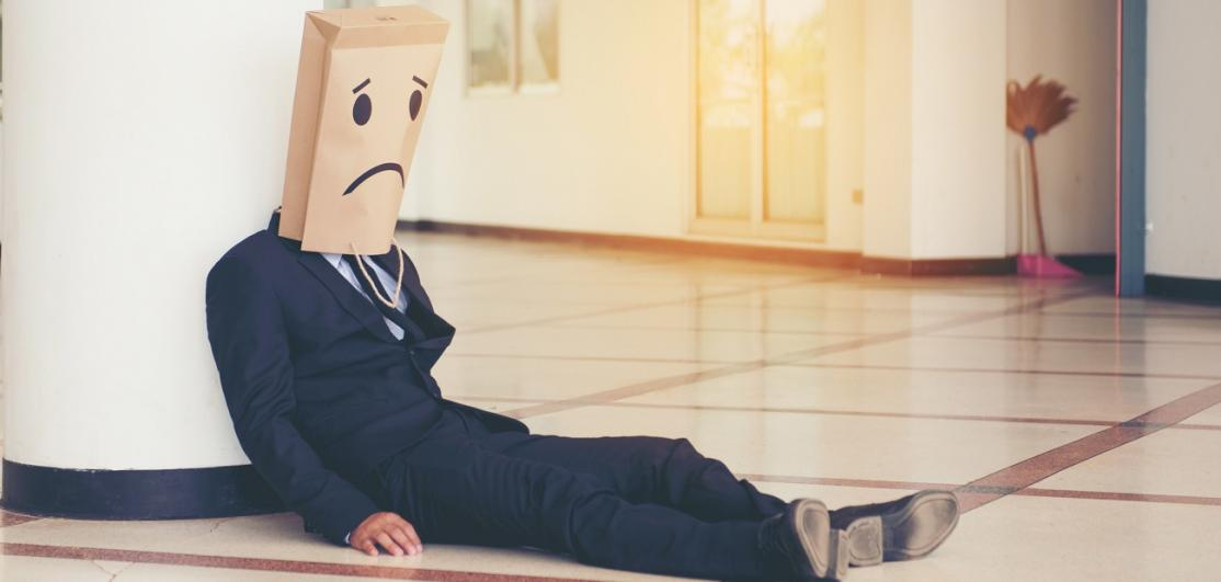 Businessman Covering Face With Paper Bag While Sitting On Floor