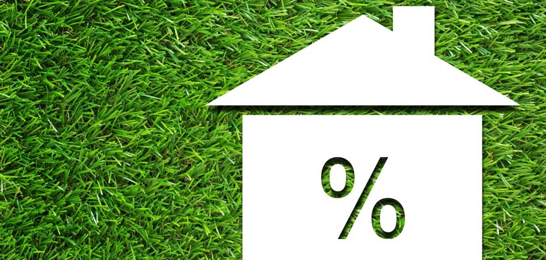 White house and interest rate symbol on green grass background