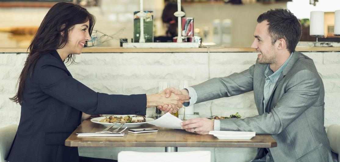 Businessman and businesswoman shaking hands at restaurant table