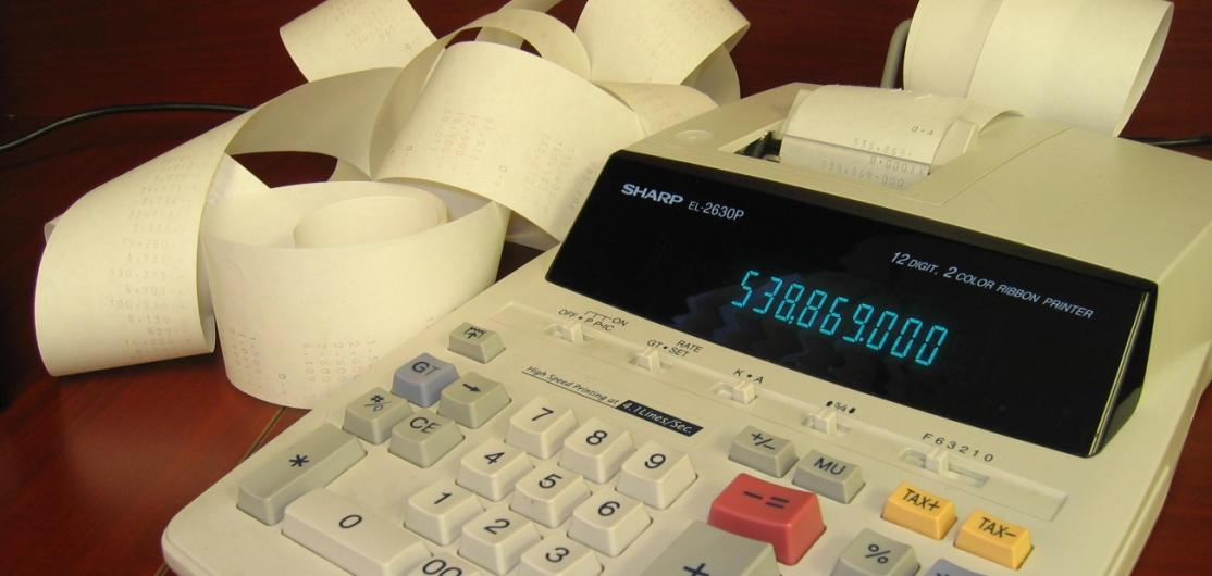 A calculator with a trail of calculations on paper
