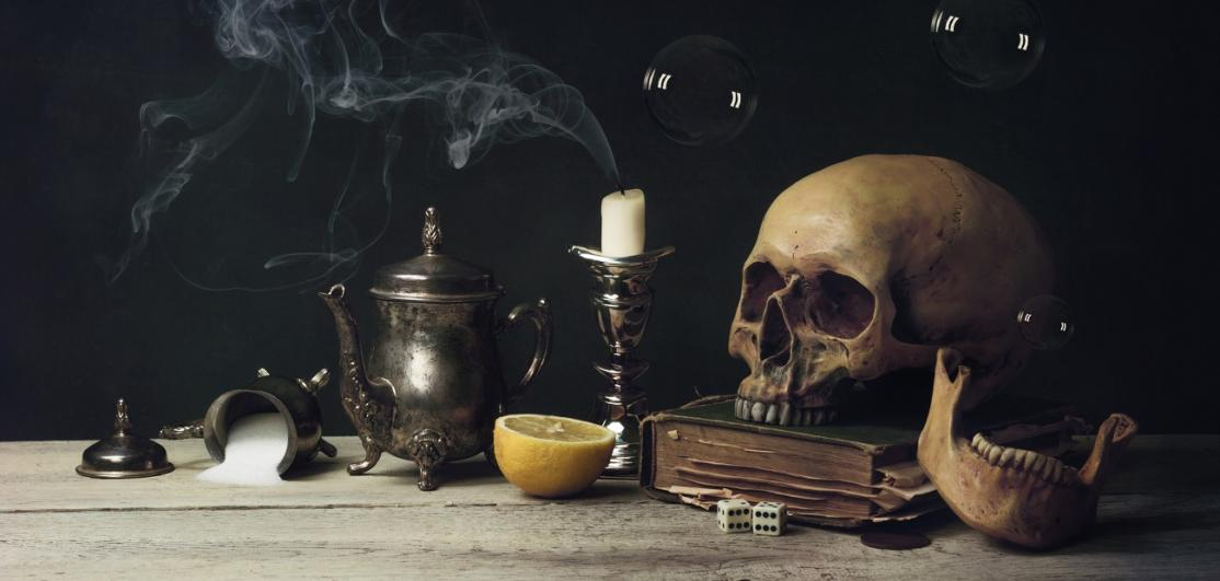 Human Skull With Lemon And Candle On Table