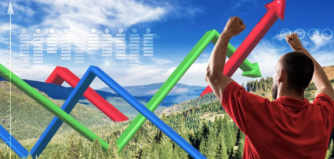 A young man with arms raised triumphantly looking at a sales chart