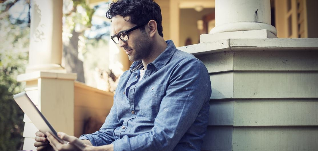 man sitting relaxing in a quiet corner of a porch, using a digital tablet